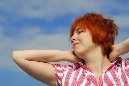 Smiling woman with red hair on blue sky background   photo