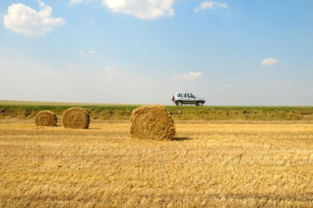 horizont: field with three rolls of straw and car on horizont line Stock Photo