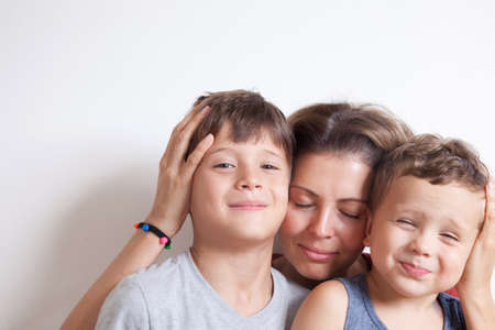 Portrait of happy mother with cute kids boy sitting on a light background. Happy family concept. Stockfoto