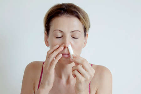 Woman with hay fever spraying nasal drops to help respiration. Concept of a healthy lifestyle and health care