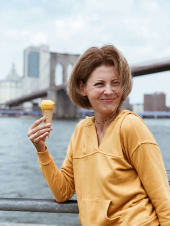 Tourist beautiful woman eating a cone of ice cream (sorbet) against the background of Manhattan skyscrapers and Brooklyn bridge. Pretty young woman eats dessert. Food concept on vacation