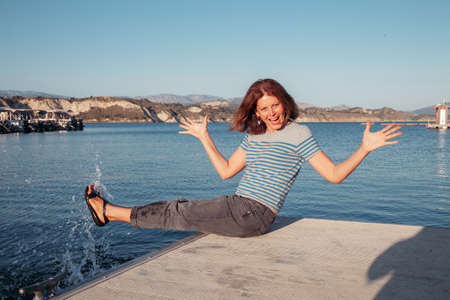 Happy young woman sitting on a pier on a lake and having fun with water.