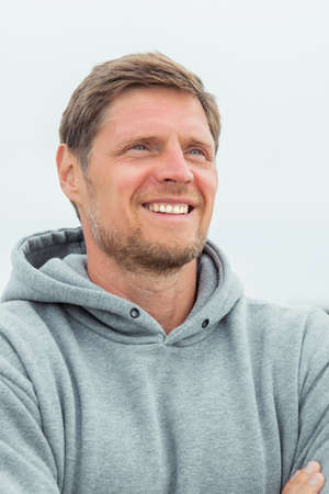 Portrait of a charming smiling man in a gray hoodie