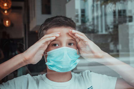 Young ill boy looking sad with protective mask at home behind window in quarantine and lockdown missing school and freedom during Covid-19 Coronavirus worldwide pandemic Stock Photo