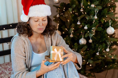 Grumpy unhappy woman is sitting next to christmas tree with gift. Woman Opens Gift and she doesn't like it.