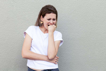 Young woman is experiencing stress and negative emotions bites her fist.