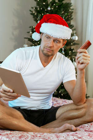 Man makes a difficult choice when buying gifts online for Christmas Stock Photo