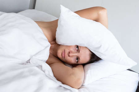 Woman suffering from noisy neighbors covers her head with a pillow. Stress and bad sleep concept