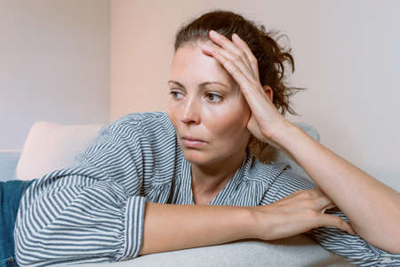 Sad woman alone at home in self-isolation quarantine to prevent social distancing of the COVID-19 coronavirus. Mental health, anxiety suppressed thinking girl. Banque d'images