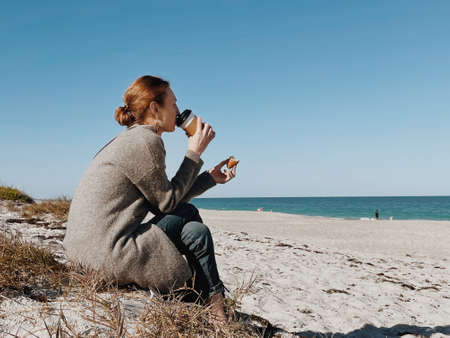 Young woman with light ginger hair and a fresh beauty, sitting quietly with a cup of coffee in the early morning, looking out at a picturesque coastline. winter and autumn travel.