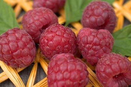 Ripe raspberries on straw plait.