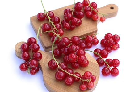 ribes: Red currants on cutting board and white background. Stock Photo