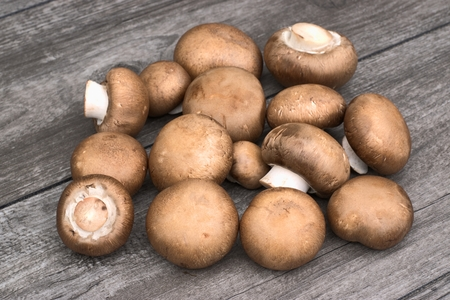 Fresh brown mushrooms on a wooden background.