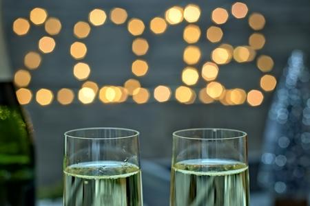 Konzept des neuen Jahres - Champagnergläser auf einem neuen Jahr des undeutlichen Goldhintergrundes.