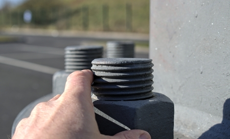 Technology, engineering, modernity and construction progress concept: A large metal screw securing a high voltage field, comparison with the hand of a man. Stok Fotoğraf