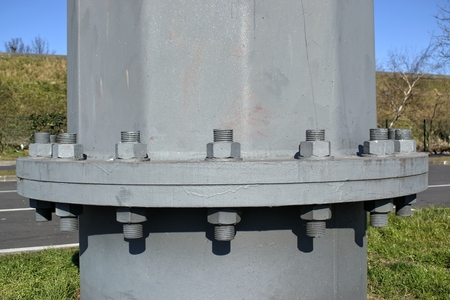 Technology, engineering, modernity and construction progress concept: large metal screw securing a high voltage pole.