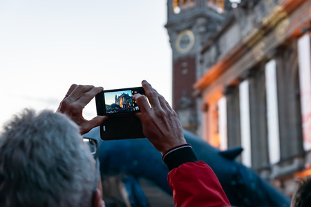 Lille, FRANCE-May 04,2019: Man who makes videos with a mobile phone Reklamní fotografie - 123061031