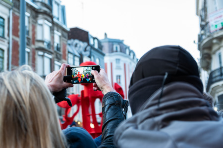 Lille, FRANCE-May 04,2019: Woman making video on mobile phone on the great carnival parade Lille 3000.