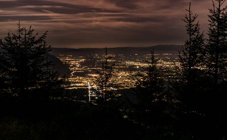 Evening top view of the city lights, French Annemasse, Swiss Geneva, dark sky background, photo with long exposure.Department of Haute-Savoie in France. Stock Photo - 132515620