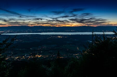Evening top view of the city lights on Lake Geneva and the blue orange sky with dark clouds after sunset, photo with long exposure.Department of Haute-Savoie in France. Stock Photo