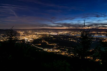 Evening top view of city lights, French Annemasse, Swiss Geneva, lake Geneva and picturesque sky with dark clouds after sunset, photo with long exposure. Department of Haute-Savoie in France.