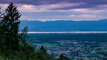 Evening view from the top of the French town Bons-en-Chablais, lake Geneva (lake Leman) and the mountains in Switzerland. Division of Haute-Savoie, region of Auvergne-Rhone-Alpes in France.