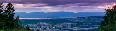 Evening panorama view from the top of the French town Bons-en-Chablais, lake Geneva (lake Leman) and the mountains in Switzerland. Division of Haute-Savoie, region of Auvergne-Rhone-Alpes in France. Stock Photo