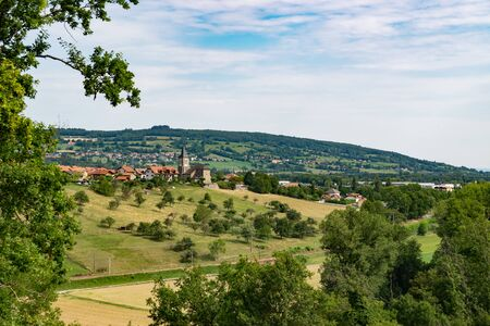 Picturesque landscape view of meadows, pastures, fields, trees, town of Brens and white clouds in the blue sky.Department of Haute-Savoie, region of Auvergne-Rhone-Alpes in France. Reklamní fotografie - 132515630