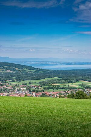 City landscape in the mountains, hills, fields, forests, green meadows, lakes in the distance and blue sky with clouds, focus area in the city.Town Bons-en-Chablais, Haute-Savoie in France. Stock Photo - 132515663