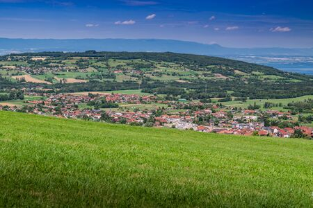 City landscape in the mountains, hills, fields, forests, green meadows, lakes in the distance and blue sky with clouds, focus area in the city.Town Bons-en-Chablais, Haute-Savoie in France.