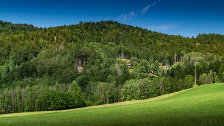Nature and landscape concept: mountain hill landscape overgrown with forests and country houses with blue sky, focus area on country houses. Haute-Savoie in France. Reklamní fotografie - 132515672