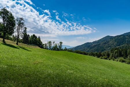 Landscape of mountain slopes covered with forests and blue sky, focus plane in the center. Haute-Savoie in France.