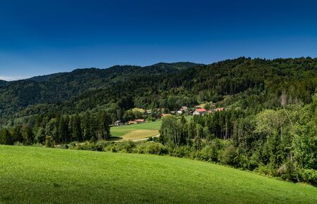 Mountain hill landscape overgrown with forests and country houses with blue sky, focus area on country houses. Haute-Savoie in France.