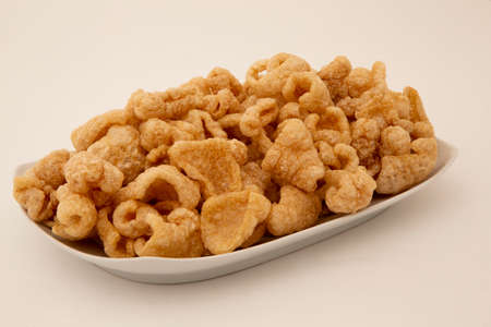 pork rind in bowl and on white background Stock Photo