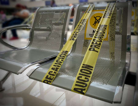 public chairs with caution tape, due to pandemic. Tape with legend caution do not use this seat Banco de Imagens