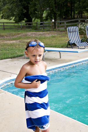A young cute swimmer wrapping in a towel after getting out of the pool with his goggles on his head. Stock Photo