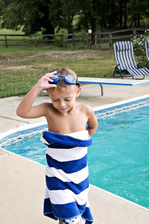 Young boy looking tired after a swim in the pool taking off his goggles. Stock Photo