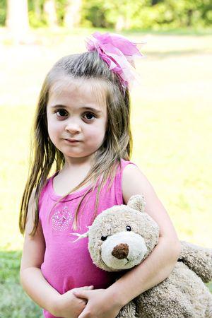Mooi meisje met haar beste vriend, haar teddybeer, op sleeptouw.
