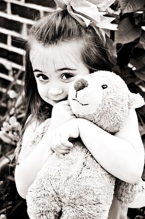 Beautiful young girl posing with her best friend, her Teddy Bear, in an outdoor setting.