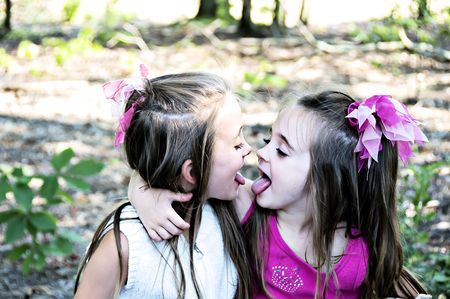 Two sisters playfully showing each other their tongues