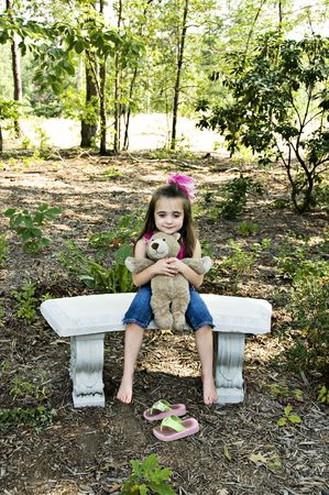 Cute little brunette girl holding her best friend a teddy bear sitting with bare feet in an outdoor setting.