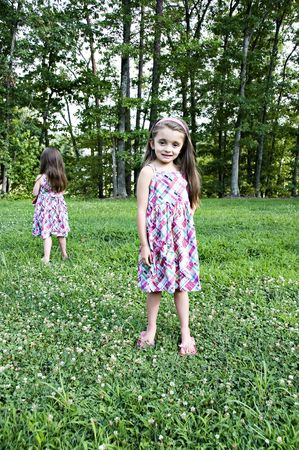 Two little girls standing in a garden with identical dresses.  One facing front and the other facing back. Stock Photo