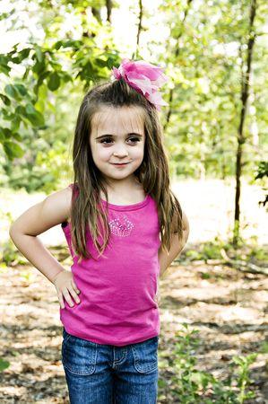Mooi meisje met een grappige glimlach stond met haar handen op haar heupen in een buitenomgeving. Stockfoto