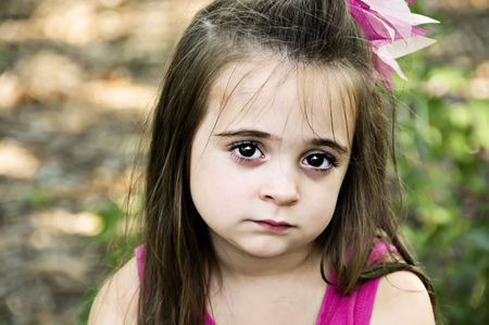 Beautiful brunette little girl posing with a sad facial expression.