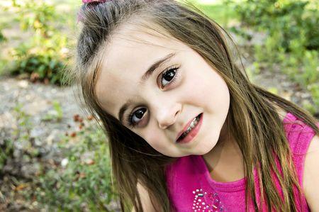 Grote bruine ogen, close-up, en een mooi kind, gekleed in roze met lange brunette haar.