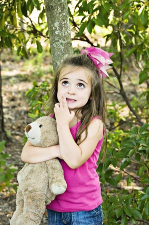 Little girl looking up with her hand next to her mouth, thinking and holding her best friend, her teddy bear.