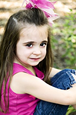 knees up: Cute little girl with big brown eyes and brunette long hair sitting with her knees up.