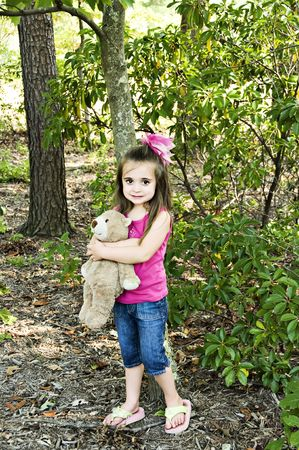 Beautiful little girl standing in the garden holding her best friend, her teddy bear.