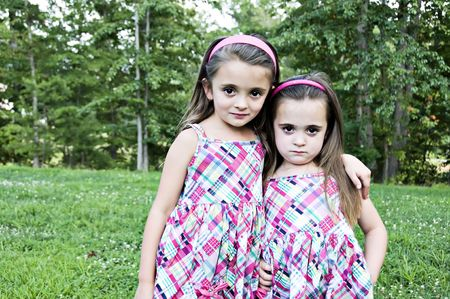 Best Friends and sisters  looking as if they might be up to something.  They are beautiful little girls with sweet expressions.   They have brown hair and brown eyes and are wearing pink plaid sundresses.