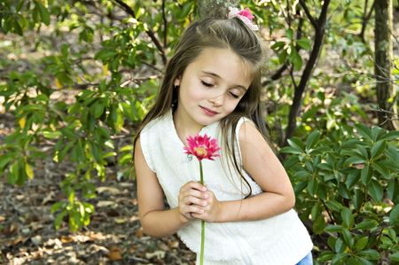 Little girl holding a pink flower with a look of love on her face.